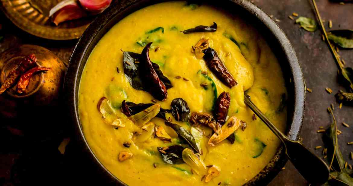 Palak Dal in a bowl with tadka ingredients on top and around