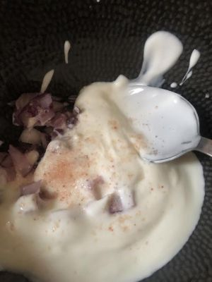 Plain yoghurt, red onion and salt in bowl
