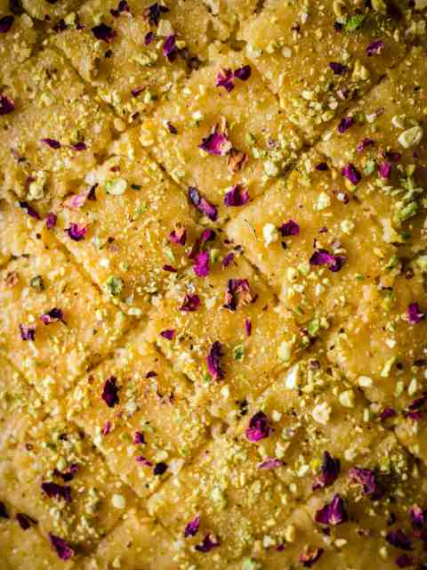 Baklava traybake cut into diamond shapes with pistachio and rose petals scattered on top