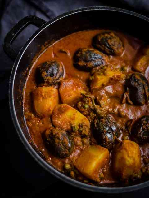 Aloo Baingan curry in black pot on grey towel