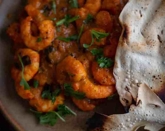 Prawn Masala in plate with papadum to side