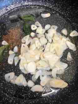 Sliced garlic added to oil in pan