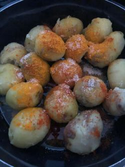 Turmeric, red chilli and salt on potatoes in hot oil