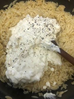 Sauce and Orzo in pot being stirred with spoon