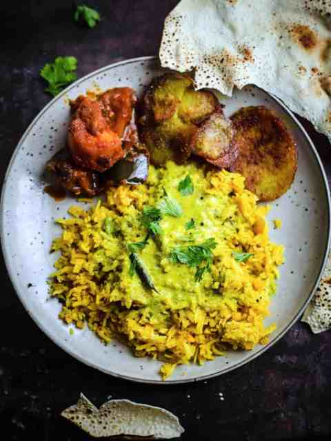 Kadhi Khichdi in a plate with papadums, potatoes and aubergine