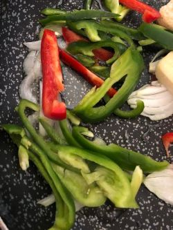 Green, red peppers, onions and garlic in wok with oil