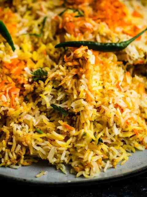 Hyderabadi Chicken Biryani in a plate with chillies and coriander on top