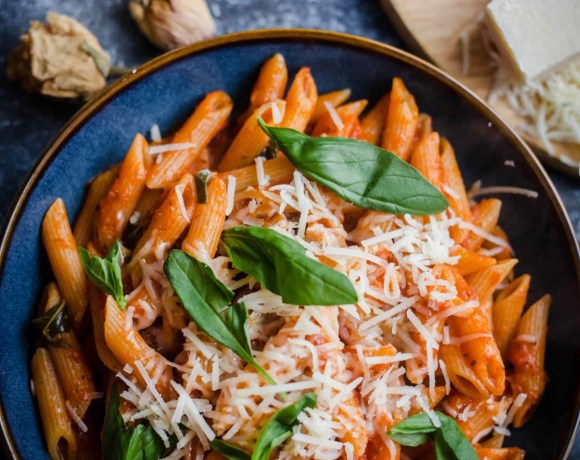 Penne Pomodoro in a bowl with parmesan and basil on top