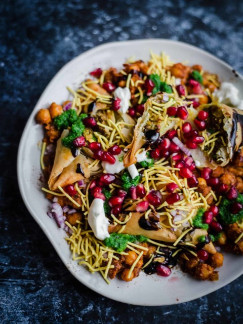 Samosa Chaat on a plate with pomegranate and sauces on top