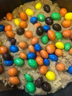 M&M added to cookie dough in cake tin