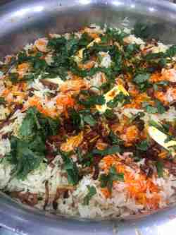 Biryani with coloured rice and coriander and fried onions on top