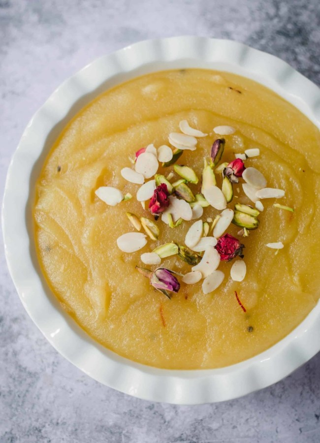 Soji Halwa in a bowl topped with flaked almonds