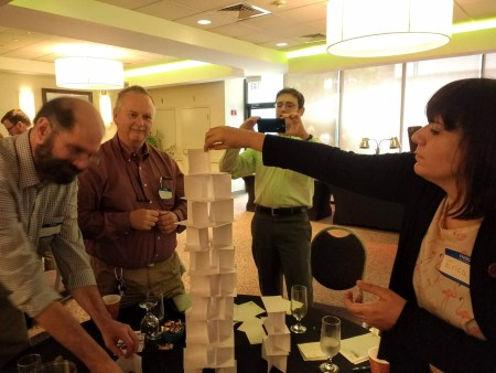 A photo showing a team of educators building a tower out of index cards.