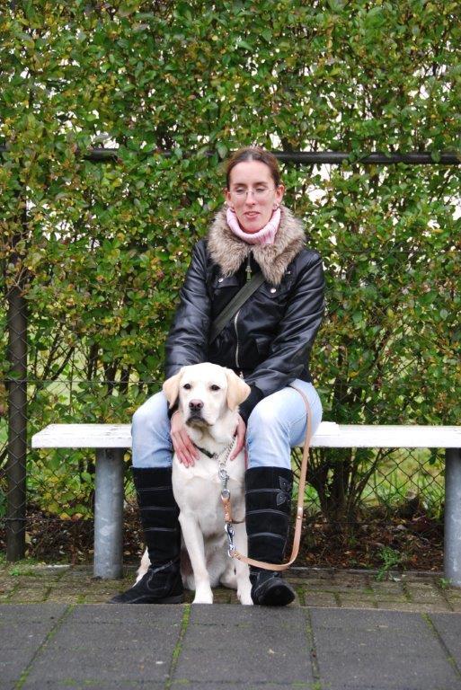Foto van Debby, die tijdens de schoolinstructie in december 2009, op een bankje zit bij KNGF Geleidehonden met tussen haar benen een zittende zeer blonde labrador, Umbar.