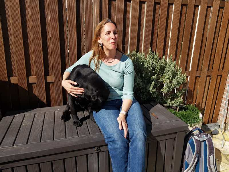 Foto van zwarte labrador Tarka, die naast Debby op een kussenkist in de tuin zit.
