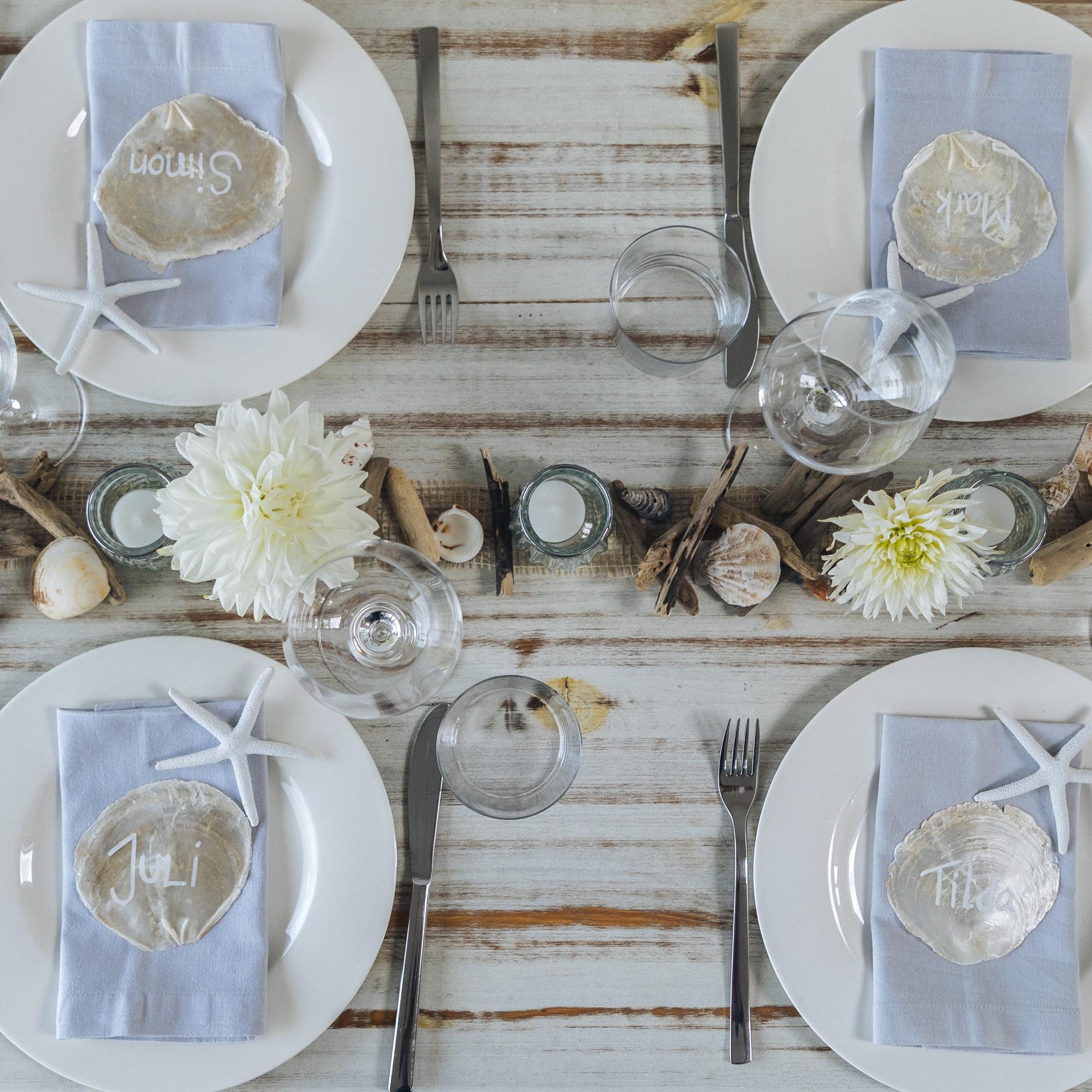 Tisch-Deko mit Schwemmholz: maritim gedeckter Tisch von oben fotografiert mit Teelichtern, Muscheln und Dahlien