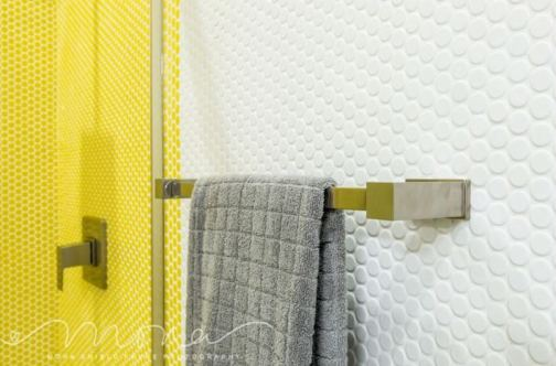 Light and bright, yellow and white penny round mosaic tiles offer a playful setting in this bathroom's design. Photo courtesy of Mona Shield Payne Photography.