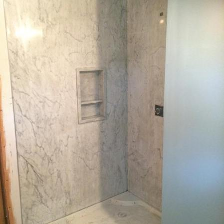 Bianco Carrara Bolder Stone Panel installed in a shower with a stone niche