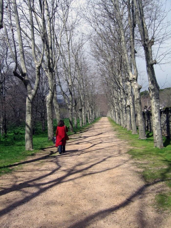 Anniqua in a red coat walking toward Monasterio Real de San Lorenzo de El Escorial