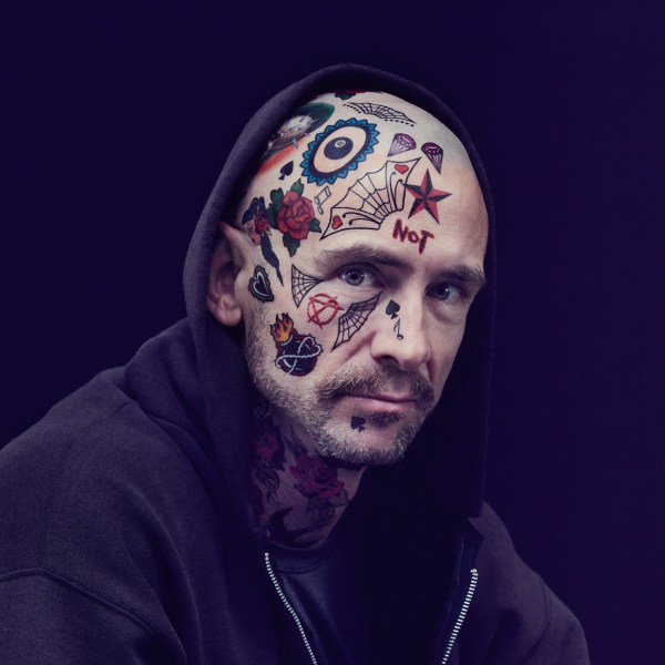 Chuck Palahniuk in a black hoodie with half his face covered in tattoos.