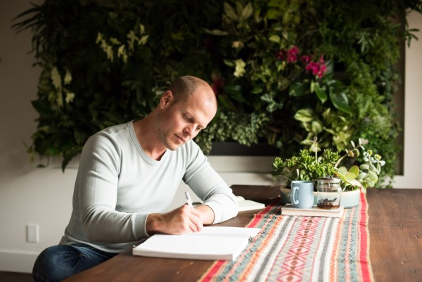 Tim Ferriss sitting at a table with plants behind him and writing in a notebook.
