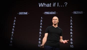 """Tim Ferriss giving his Fear-Setting TED talk in front of a slide that has """"What if I?"""" at the top and 3 columns below it: Define, Prevent, and Repair."""