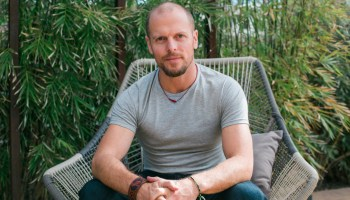 Tim Ferriss sitting in a large patio chair in front of a large patch of bamboo.