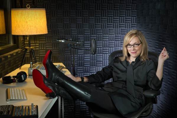 Debbie Millman sitting at a desk with her feet up in black boots with red soles.