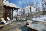 Exterior, horizontal, rear patio with built in hot tub looking out to ski slope and mountain