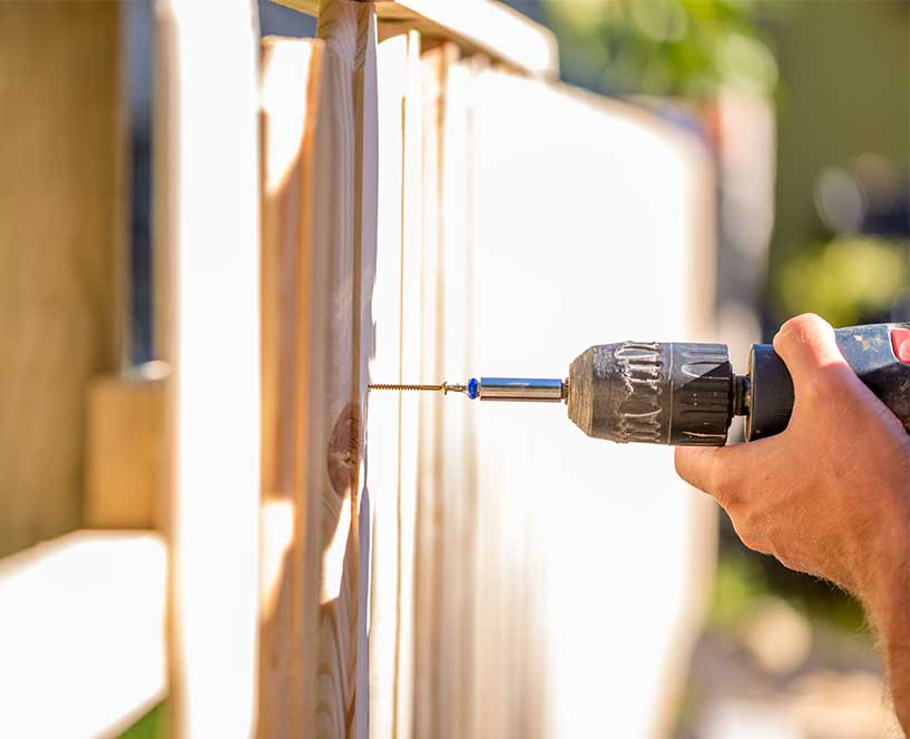 Repairing a wooden fence with a drill gun in San Ramon