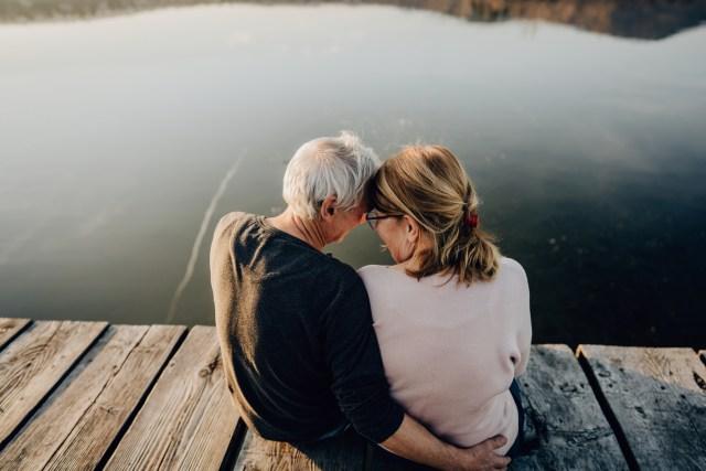 Couple sitting on the dock enjoying the lake.
