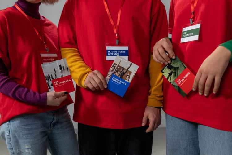 people holding red brochure