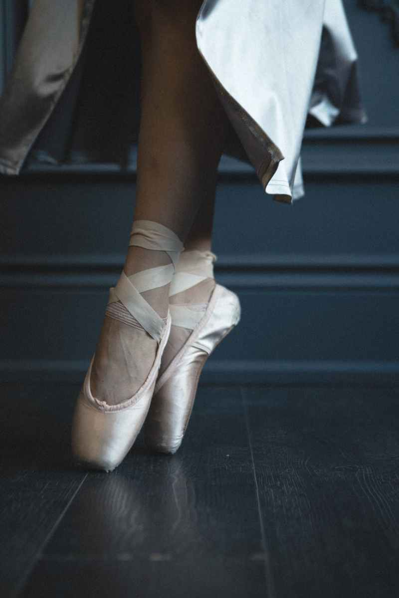 photo of woman wearing ballet shoes