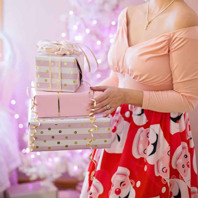 woman wearing pink v neck long sleeved shirt and red skirt holding christmas gifts