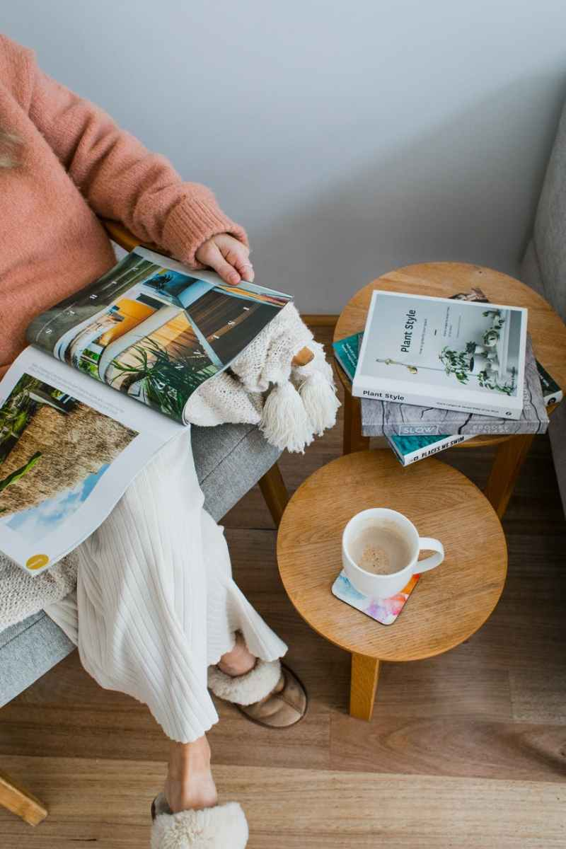 unrecognizable woman reading magazine in armchair near table with mug