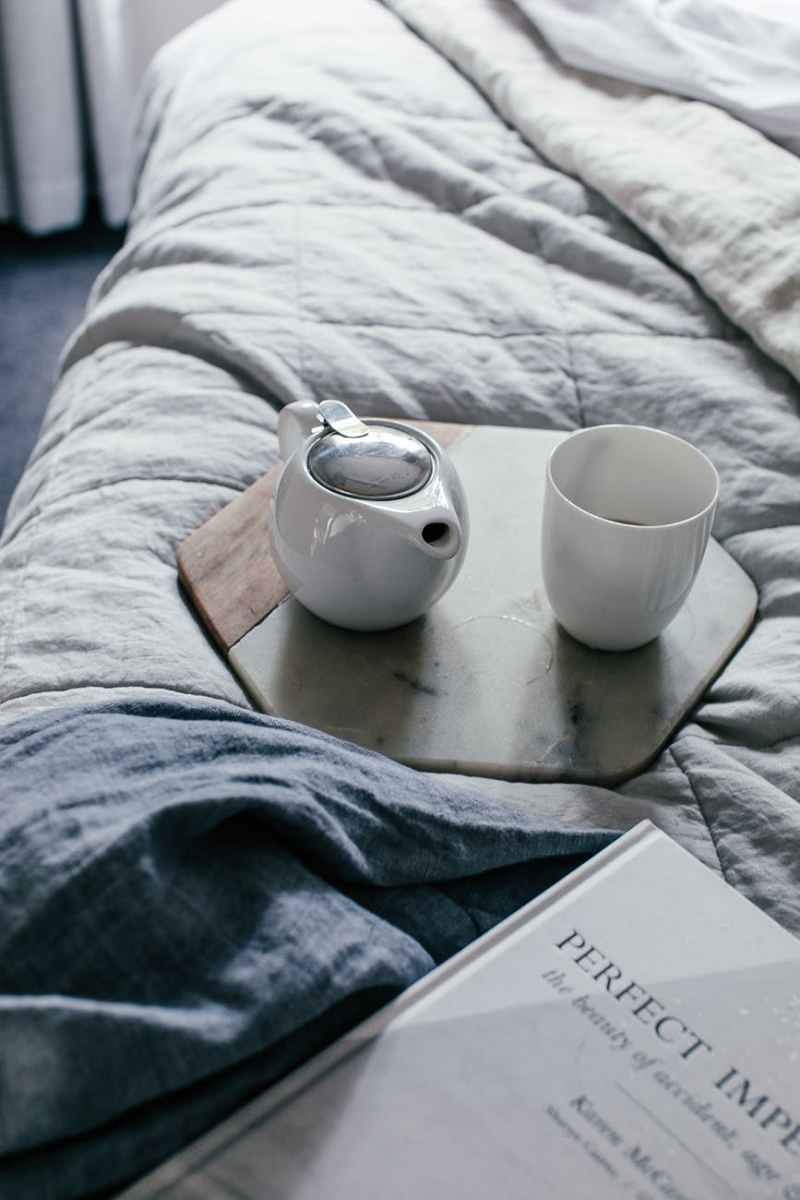 cup and teapot on tray on bed