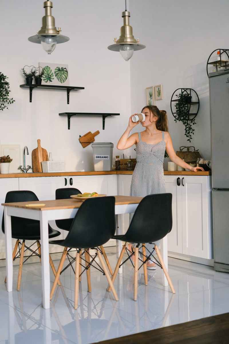 young woman drinking beverage in kitchen in morning