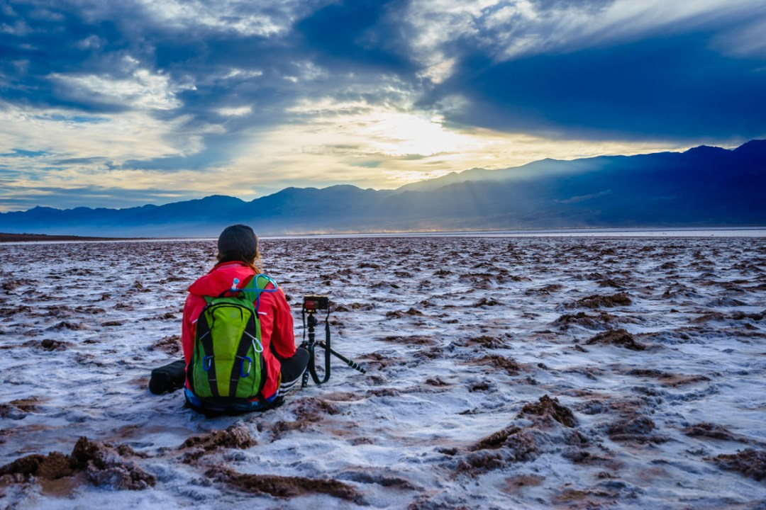 Hiker watches sunset of the salt flats at Badwater Basin.