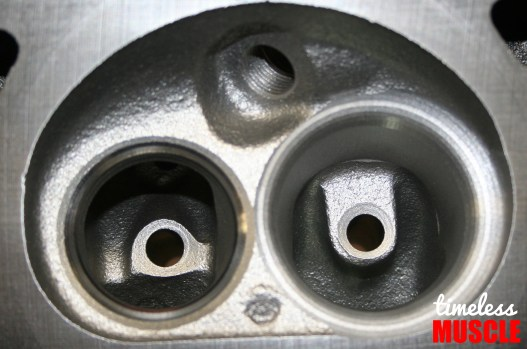 As manufactured, the intake and exhuast ports are clogged with rough surfaces and thick casting bosses around the valve guides.