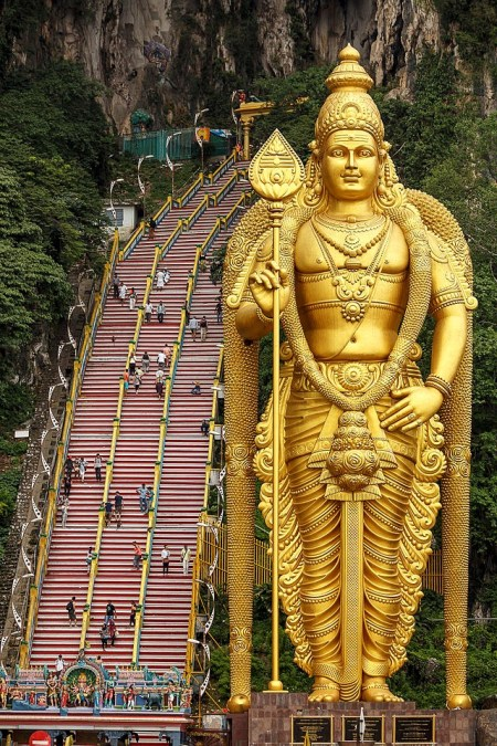 42.7 metres high gold painted statue of Muruga stands at the foot of 272 steps that leads to the temples within the limestone hill, Batu Caves, Kuala Lumpur