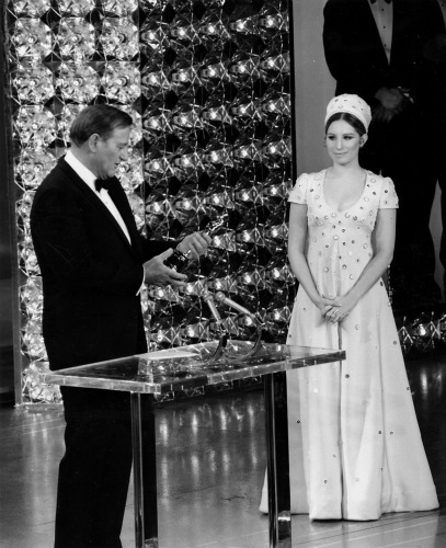 John Wayne accepts his Oscar as presenter Barbra Streisand looks on.