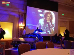 Classic 80's videos blast on the screen as the DeLorean Time Machine rental car stands ready to accept party guests.