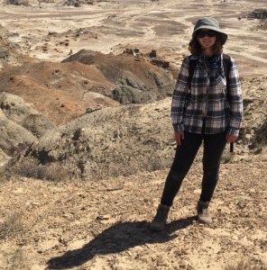 Charlotte Hohman stands in front of badlands dressed for fieldwork, including hat and backpack