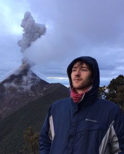Photo showing Benjamin in the foreground with a volcano erupting the background