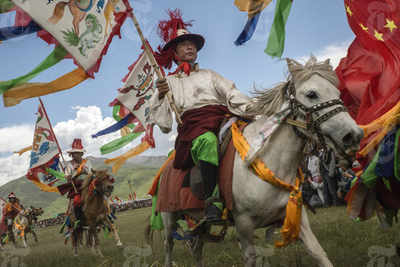 Tibetan horsemen display their skills at a government-organized horse festival in Yushu, China, July 26, 2015. (Image courtesy: The New York Times)