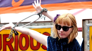 Miss Hadley shows locked wrists outside Worlds of Wonder tent at San Diego County Fair.