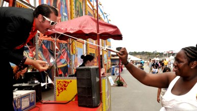 Volunteer pulls out sword outside Worlds of Wonder tent at San Diego County Fair.