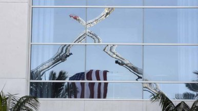 Two fire ladders with a flag are reflected in the Hilton San Diego Bayfront.