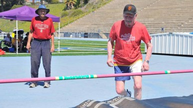 "Don Pellmann makes his approach in the high jump as Olympian Franklin ""Bud"" Held looks on. Photo by Chris Stone"