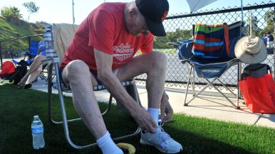 Pellmann laces up his comfortable shoes before the long jump competition. Photo by Chris Stone